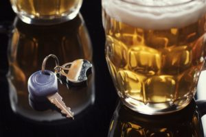 Beer and car key on black table